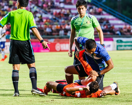 physiotherapists: SISAKET THAILAND-JULY 23: First aid team of Sisaket FC. (blue) in action during Thai Premier League between Sisaket FC and Songkhla Utd at Sri Nakhon Lamduan Stadium on July 23,2014,Thailand Editorial