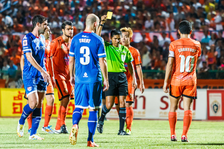warned: SISAKET THAILAND-AUGUST 13: The referee (green) show a yellow card during Thai Premier League between Sisaket FC and PTT Rayong FC at Sri Nakhon Lamduan Stadium on August 13,2014,Thailand Editorial