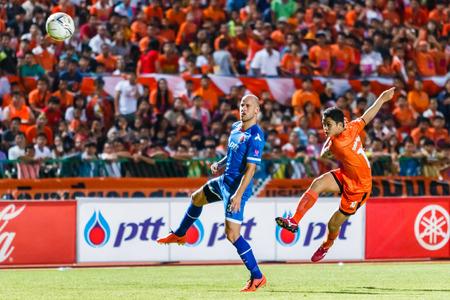 premier league: SISAKET THAILAND-AUGUST 13: Sarayuth Chaikamdee of Sisaket FC. (orange) shooting ball during Thai Premier League between Sisaket FC and PTT Rayong FC at Sri Nakhon Lamduan Stadium on August 13,2014,Thailand