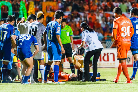 SISAKET THAILAND-AUGUST 13: First aid team of Sisaket FC. (white) in action during Thai Premier League between Sisaket FC and PTT Rayong FC at Sri Nakhon Lamduan Stadium on August 13,2014,Thailand