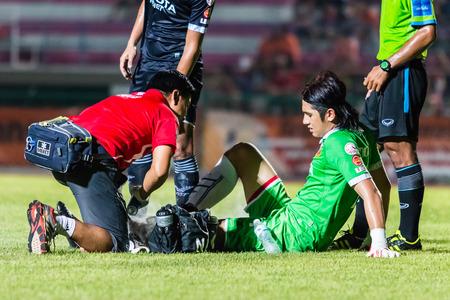 physiotherapists: SISAKET THAILAND-September 21: Pathomtat Sudprasert of Roi Et Utd. injured during Friendly Match between Sisaket FC and Roi Et Utd at Sri Nakhon Lamduan Stadium on September 21,2014,Thailand Editorial