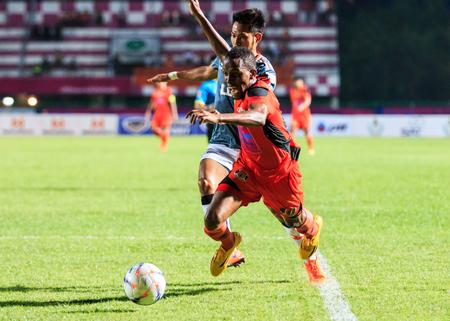 chiangrai: SISAKET THAILAND-MAY 3: Adefolarin Durosinmi of Sisaket FC. (orange) in action during Thai Premier League between Sisaket FC and Chiangrai Utd. at Sri Nakhon Lamduan Stadium on May 3,2015,Thailand Editorial