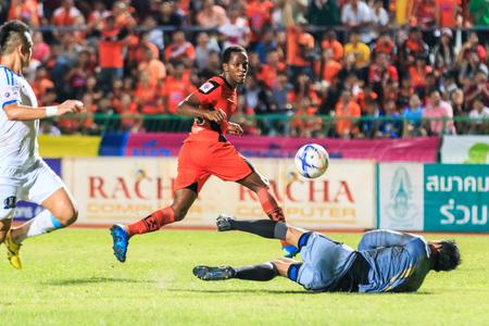 tot: SISAKET THAILAND-SEPTEMBER 20: Adefolarin Durosinmi of Sisaket FC. (orange) shooting ball during Thai Premier League between Sisaket FC and TOT SC at Sri Nakhon Lamduan Stadium on September 20,2015,Thailand
