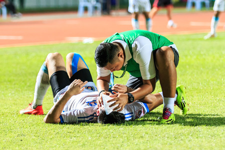 SISAKET THAILAND-SEPTEMBER 20: First aid team of TOT SC (green) in action during Thai Premier League between Sisaket FC and TOT SC at Sri Nakhon Lamduan Stadium on September 20,2015,Thailand