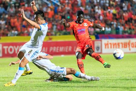 oj: SISAKET THAILAND-SEPTEMBER 20: O.J. Obatola of Sisaket FC. (orange) shooting ball during Thai Premier League between Sisaket FC and TOT SC at Sri Nakhon Lamduan Stadium on September 20,2015,Thailand