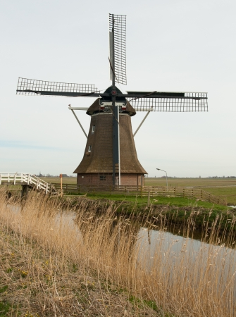 wind powered building: A traditional dutch windmill near a canal
