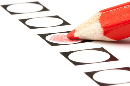 filling in: Voting form with red pencil filling in a black circle