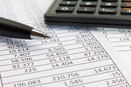 stocks and shares: A calculator and pen on financial papers Stock Photo