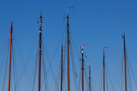 An Image of ships masts in a harbour against a blue sky photo