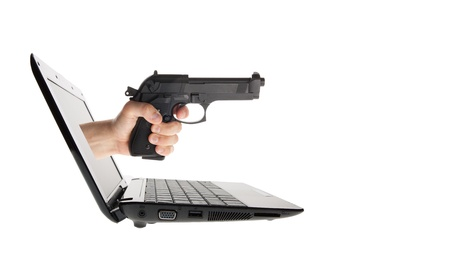 Laptop and hand with gun sticking out isolated on white photo