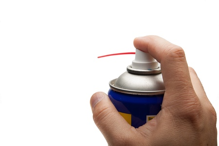 lubricant: hand pushing spray can. isolated over white background