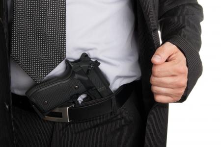 Man in suit showing gun tucked in pants