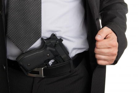 Man in suit showing gun tucked in pants photo