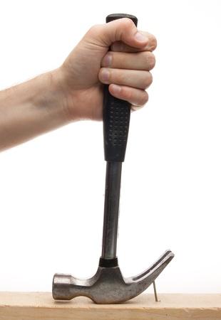 the hammer: Mano sacando un clavo con un martillo sobre fondo blanco Foto de archivo