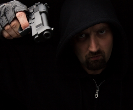 Gangster with gun against a black background Stock Photo - 14659872
