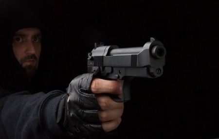 Masked robber with gun against a black background Stock Photo