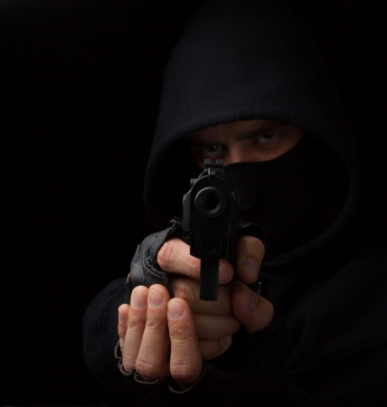 Robber with gun aiming into the camera against a black background Archivio Fotografico