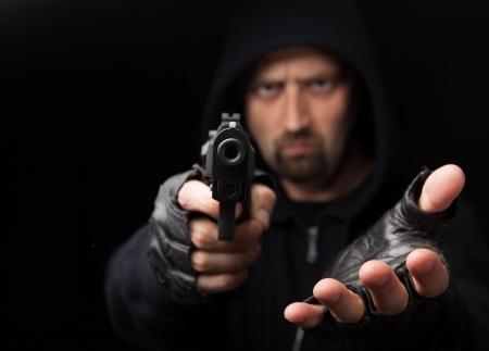 Ladrón con el arma extendiendo la mano contra un fondo negro