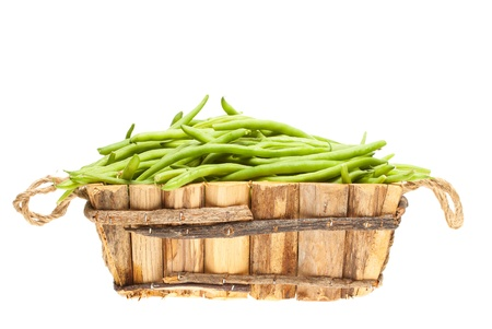 bunch of green beans in a wooden basket on a white background photo