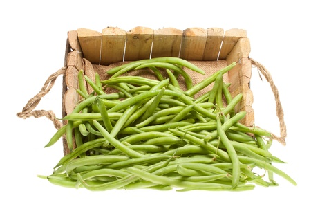 Bunch of green beans coming out of a wooden basket on a white background photo
