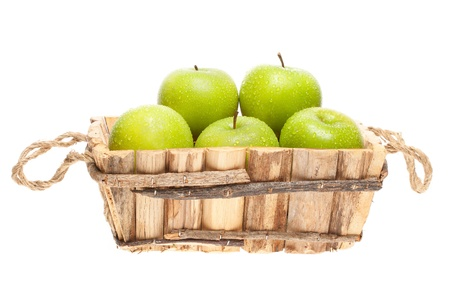 freshly harvested Granny Smith apples in a wooden basket on a white background photo