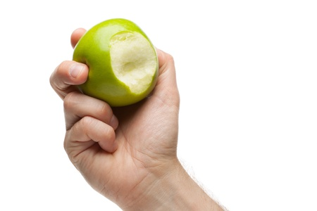 missing bite: Hand holding green apple with bite missing on a white background