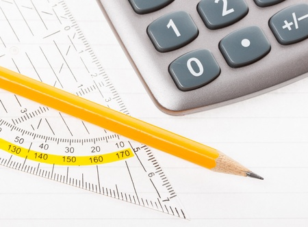 close-up of protractor, calculator, and pencil on paper