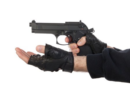 Robber with gun holding out hand against a white background