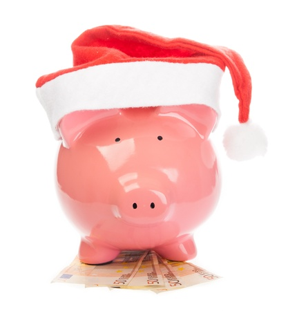 Piggy bank with christmas hat standing on euros. photo