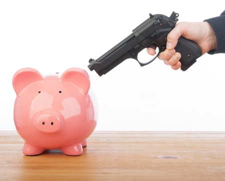 Man pointing a gun at a piggy bank photo