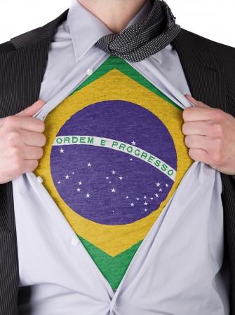 Business man rips open his shirt to show his Brazilian flag t-shirt