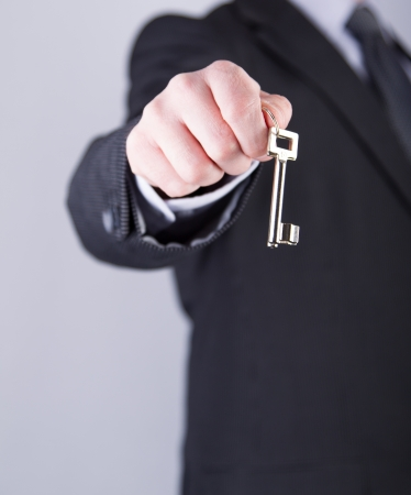 A real estate agent holds out a key of a new home to a lucky buyer photo