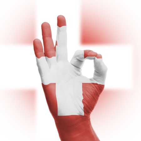hand OK sign, wrapped in the flag of Switzerland photo