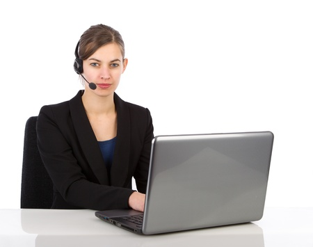Attractive business woman with headset working on a laptop computer against a white background photo