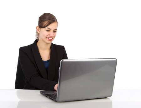 Attractive business woman working on a laptop computer against a white background photo