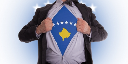 Business man rips open his shirt to show his Kosovo flag t-shirt photo