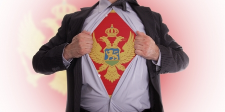Business man rips open his shirt to show his Montenegrin flag t-shirt Stock Photo - 18305007
