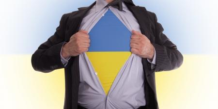 Business man rips open his shirt to show his Ukrainian flag t-shirt photo