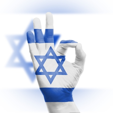 Hand OK sign, wrapped in the flag of Israel photo