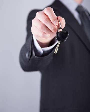 Car salesman or rental man giving a car key to someone photo