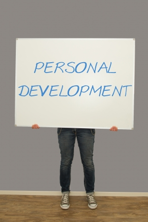Woman holding a big whiteboard with personal development written on it photo