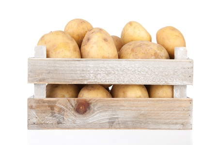 potato basket: bunch of freshly harvested potatoes in a wooden crate
