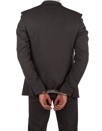 Businessman in suit and handcuffs viewed from behind isolated on white photo