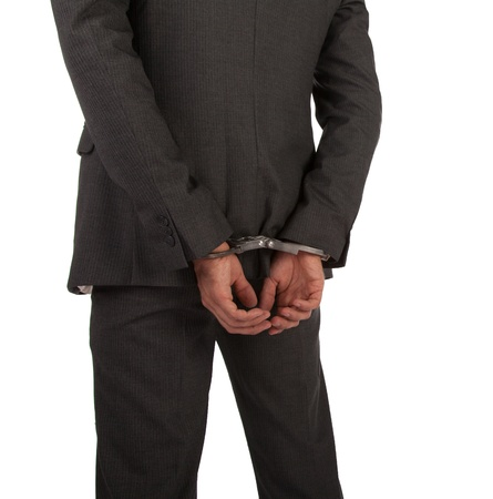 handcuffed hands: Businessman in suit and handcuffs viewed from behind isolated on white