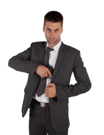 A man in a suit grabbing a gun out his jacket isolated on white