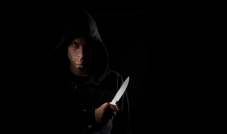A dangerous hooded man standing in the dark and holding a shiny knife photo