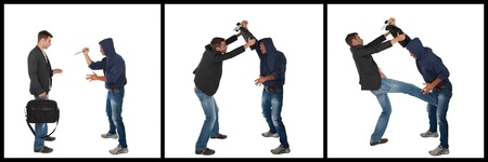 defending: Man defending himself against a knife attack using a briefcase. Self-defense concept Stock Photo