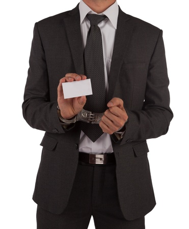 Businessman in suit and handcuffs showing a blank business card isolated on white photo