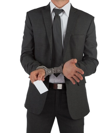 Businessman in suit and handcuffs handing over a blank business card isolated on white photo