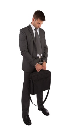 Businessman in handcuffs holding briefcase isolated on white photo